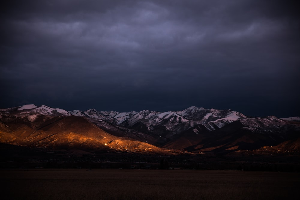 brown mountain under gray clouds during golden hour