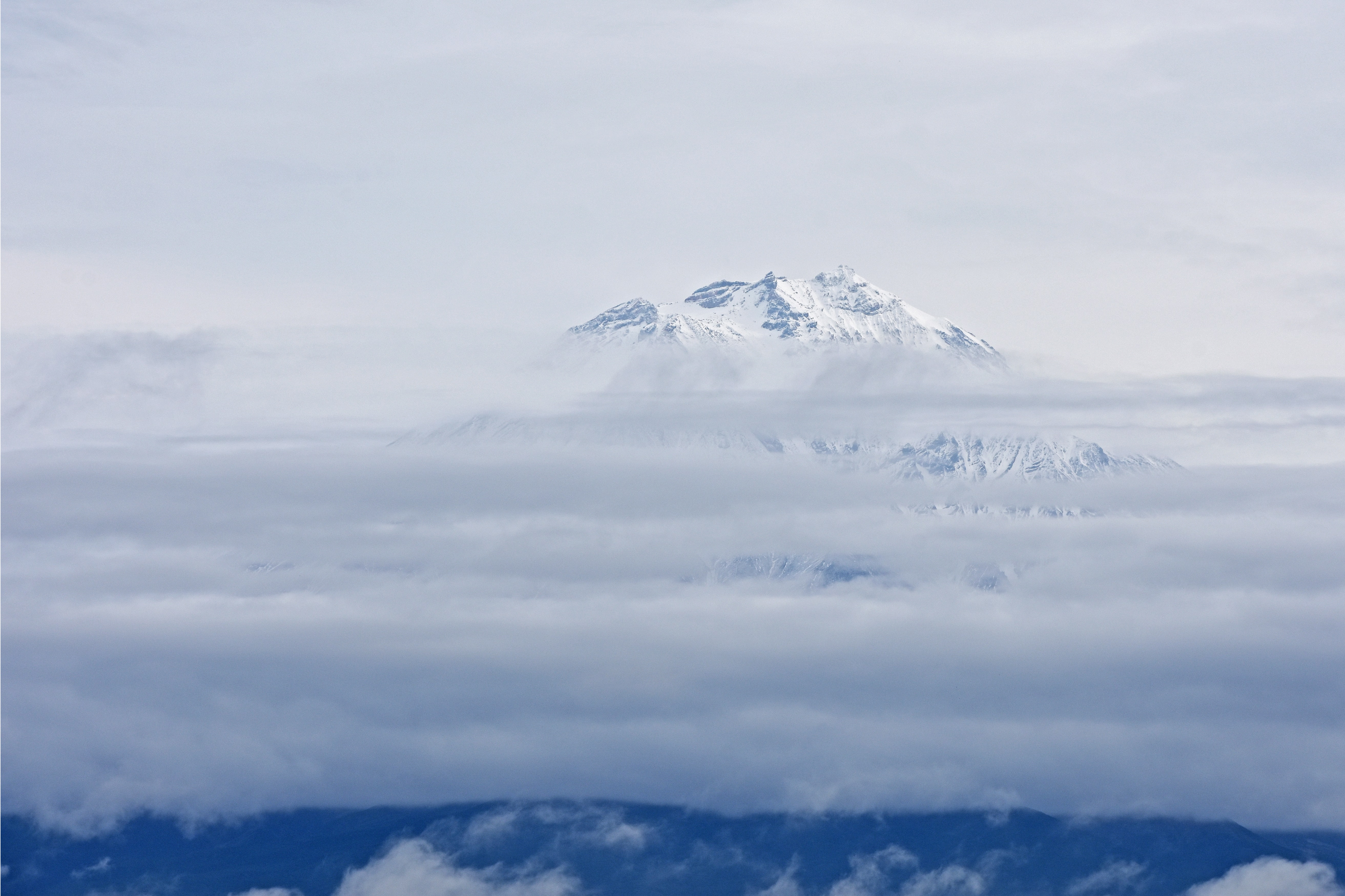 snow cap mountain surrounded by clouds at daytime