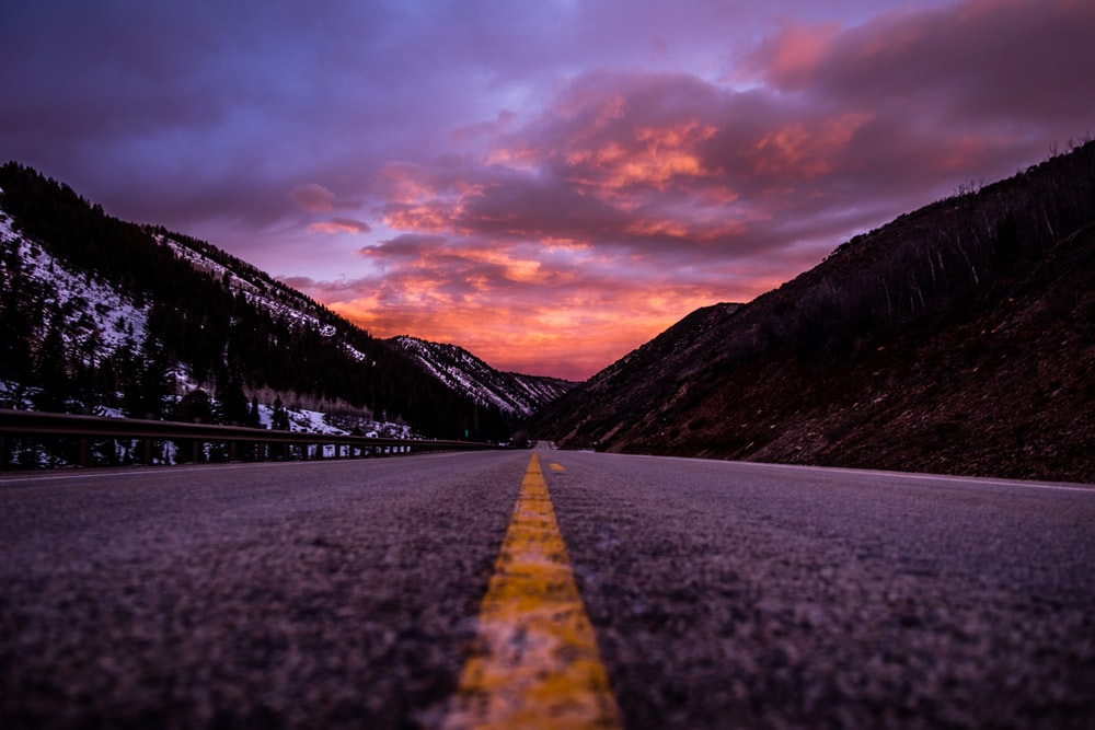 road between mountains under cloudy sky