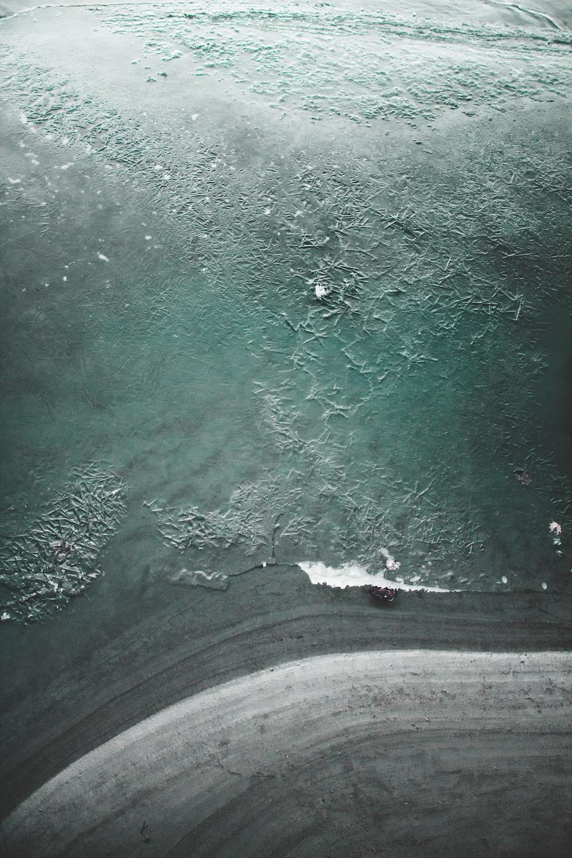 bird's eye view photo of grey sand near body of water