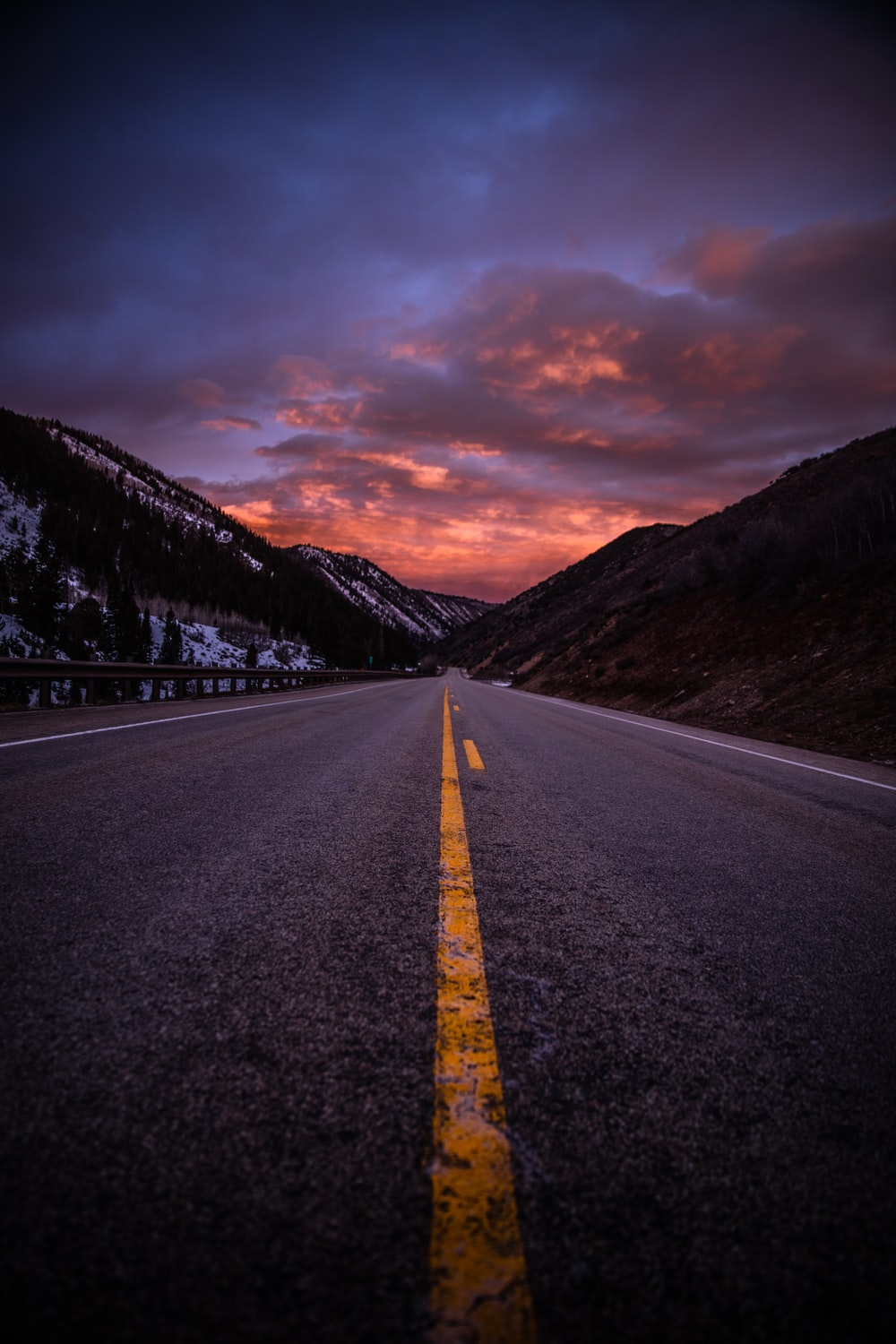 gray asphalt road between brown mountains under cloudy sky during daytime