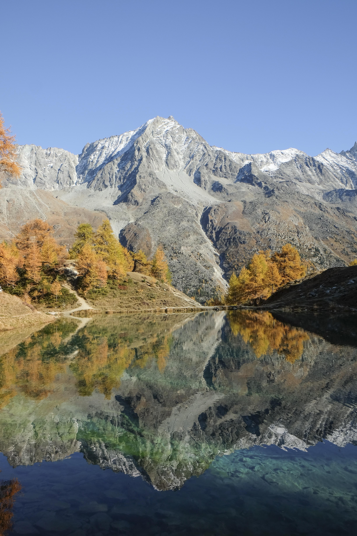 gray mountain beside body of water
