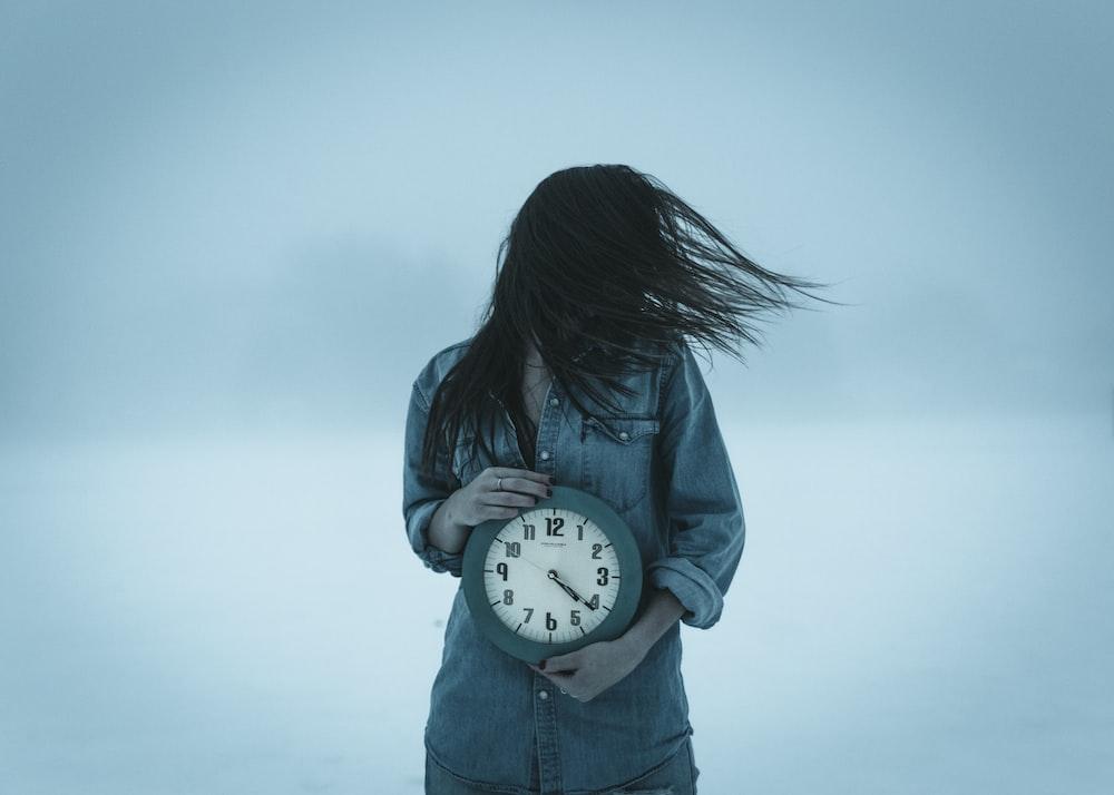 woman holding clock at 4:20