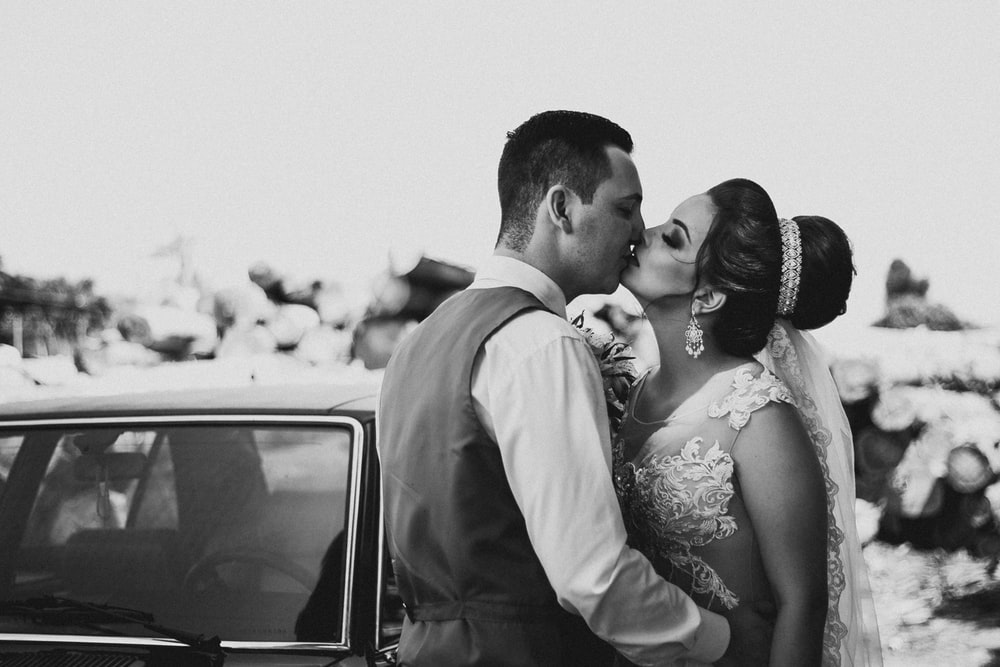 grayscale photography of bride and groom kissing beside vehicle during daytime