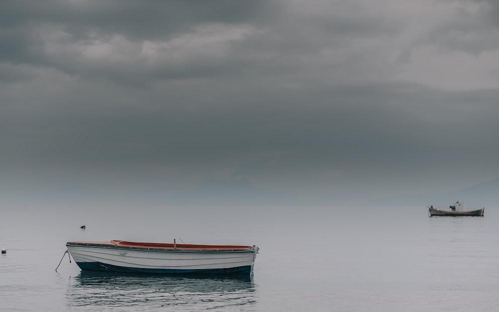 white canoe on calm sea at daytime