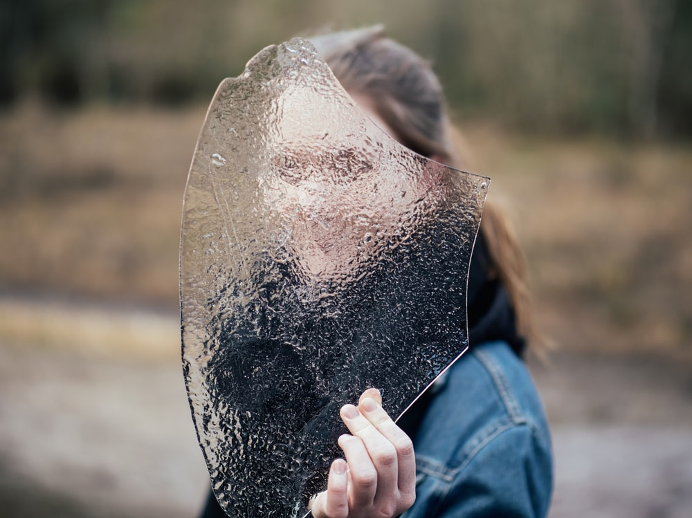 woman covering face with frosted glass