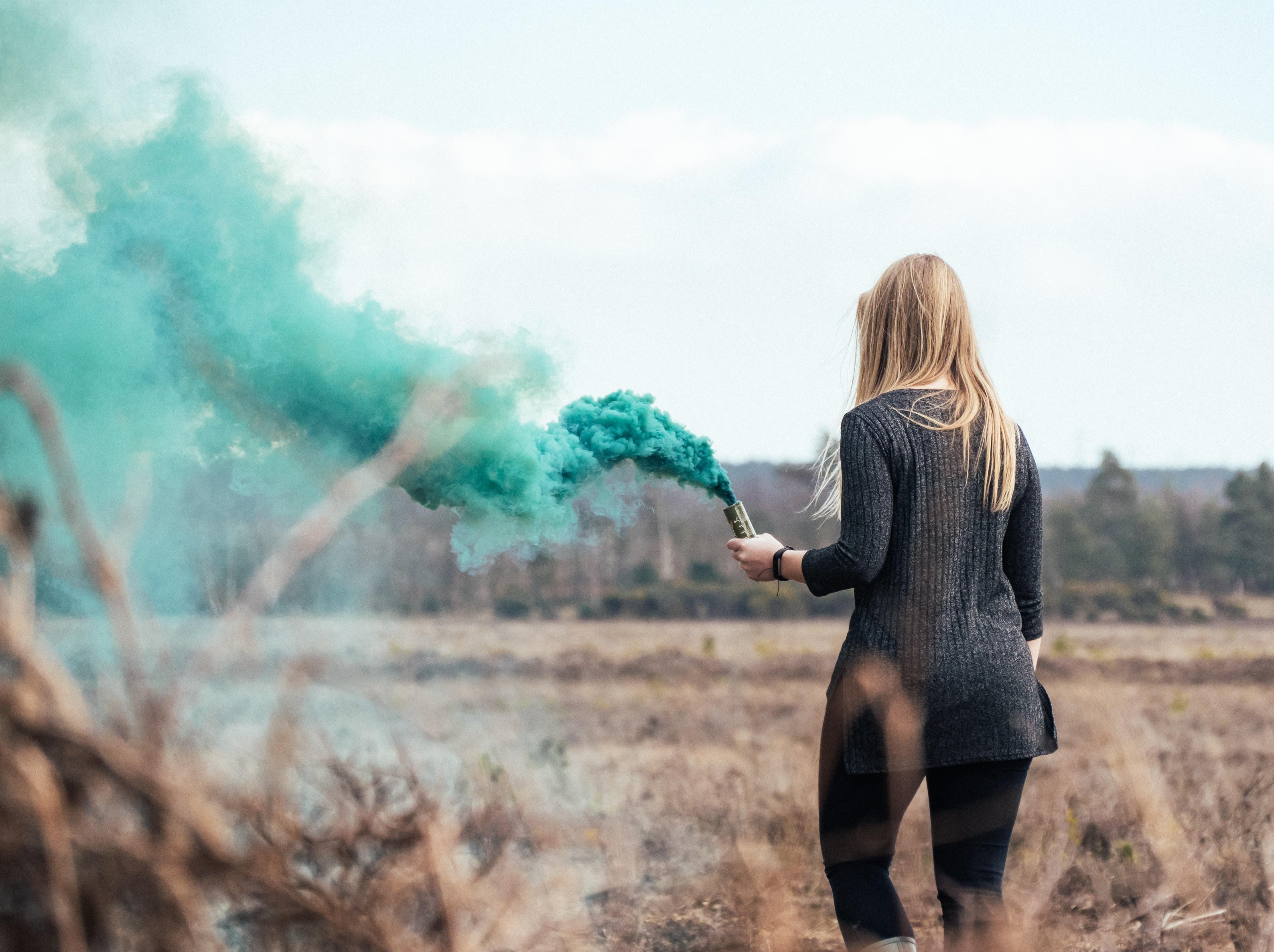 woman holding green smoke bomb
