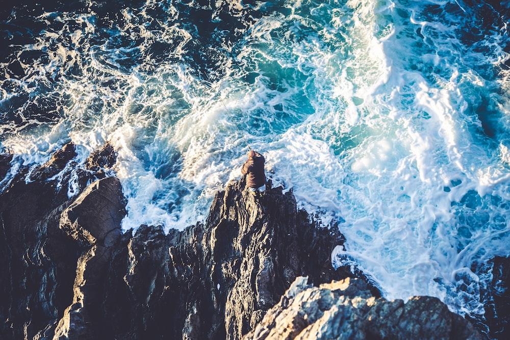 high angle photo of beach wave crushing on rocks
