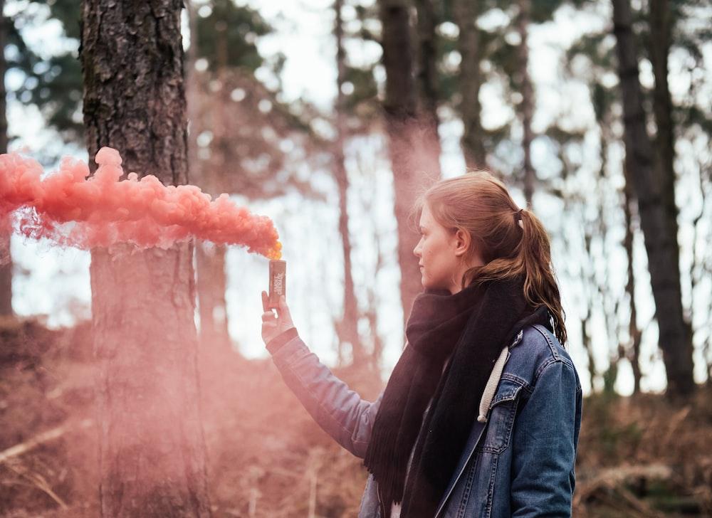 woman holding bottle blowing pink smoke