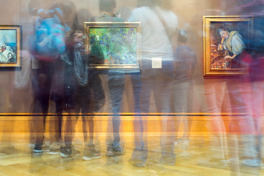 people gathering inside painting exhibit