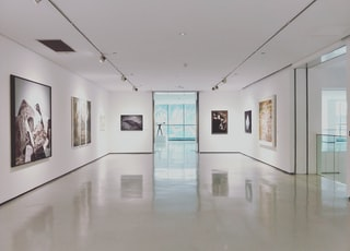 assorted paintings on white painted wall