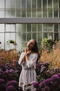 woman in standing in between purple petaled flower inside green house