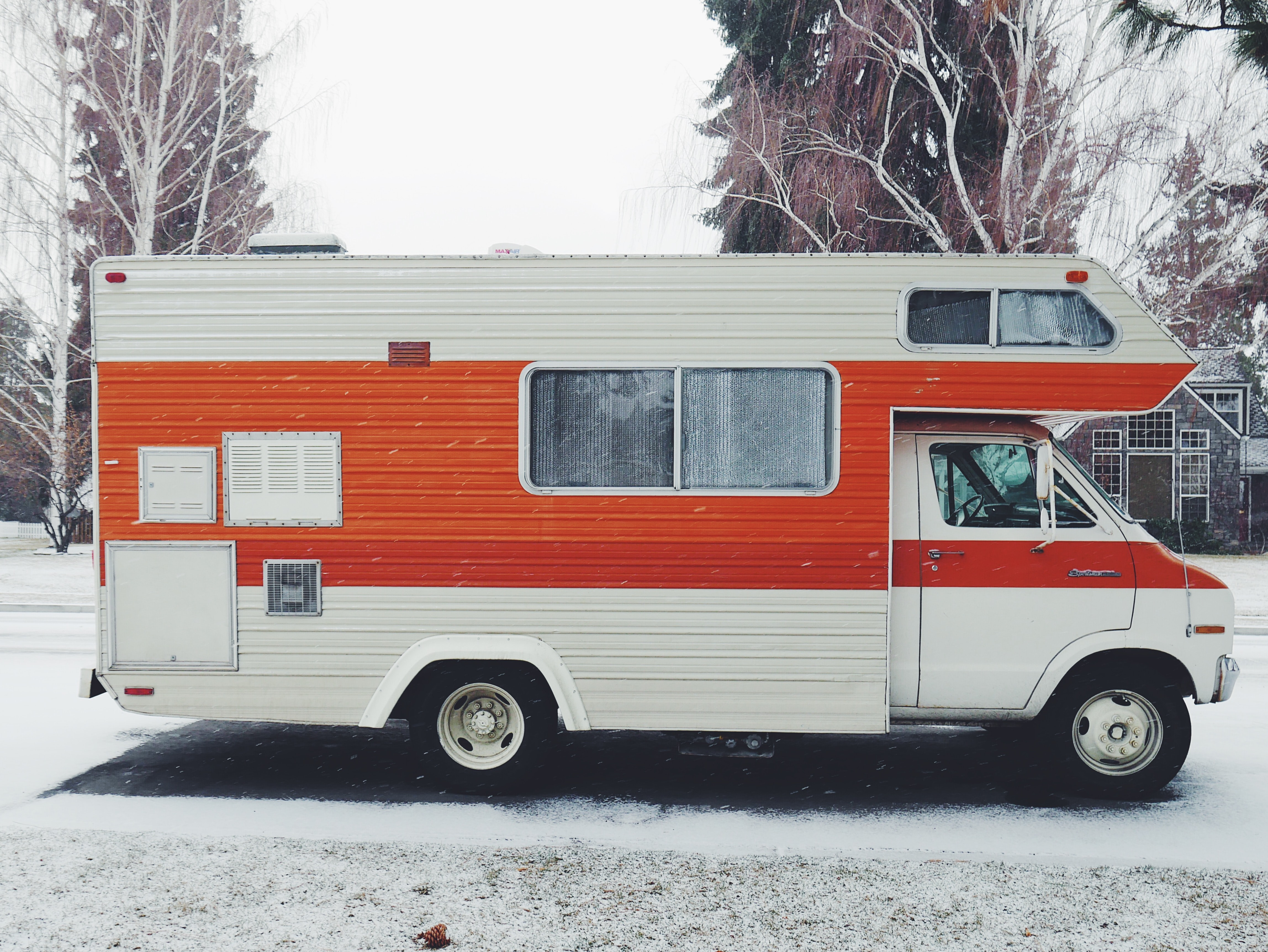 orange and white class-a motorhome surrounded by snow