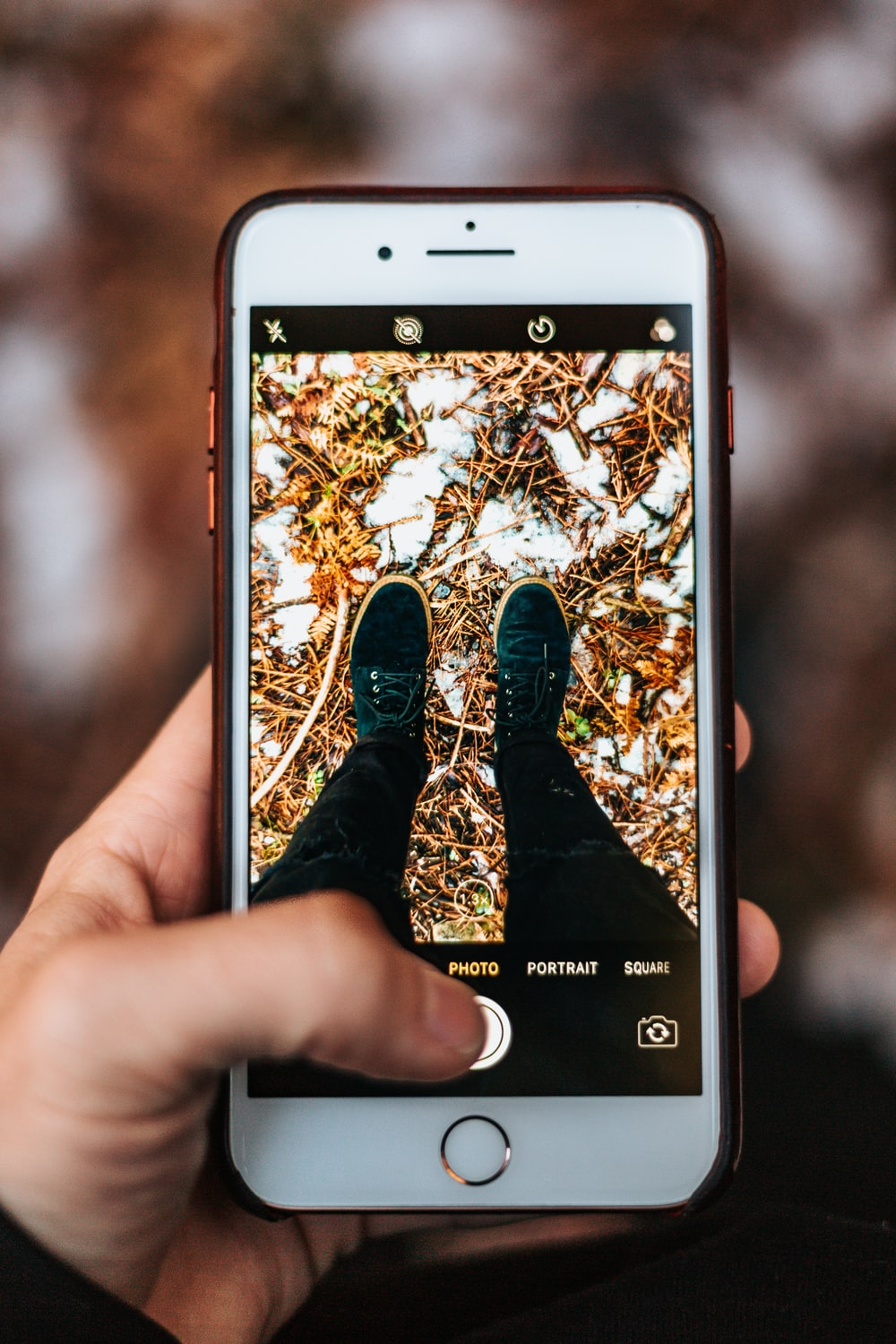 person holding iPhone taking photo of shoes