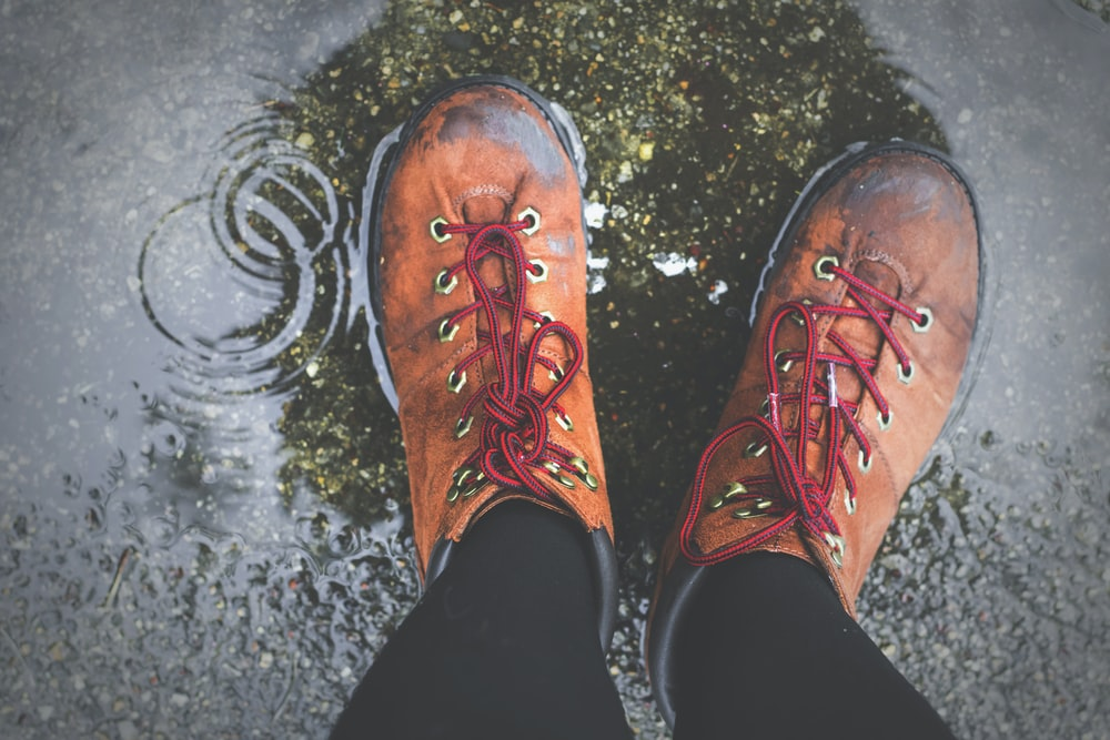 person wearing brown lace-up boots standing on wet ground