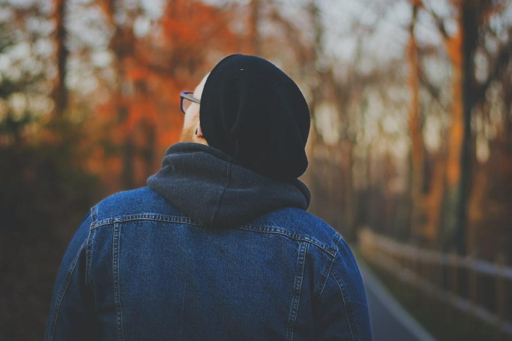 person in blue chambray hoodie walking on walkway between trees