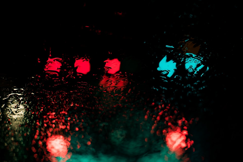 red and blue lights reflecting through body of water at nighttime
