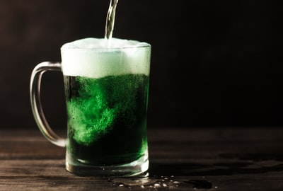 clear glass mug filled with green liquid shamrock zoom background