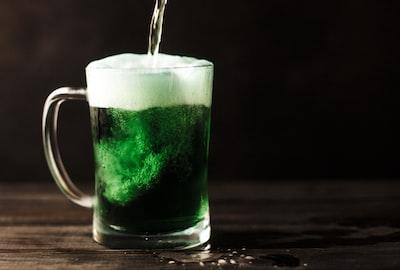 clear glass mug filled with green liquid irish teams background