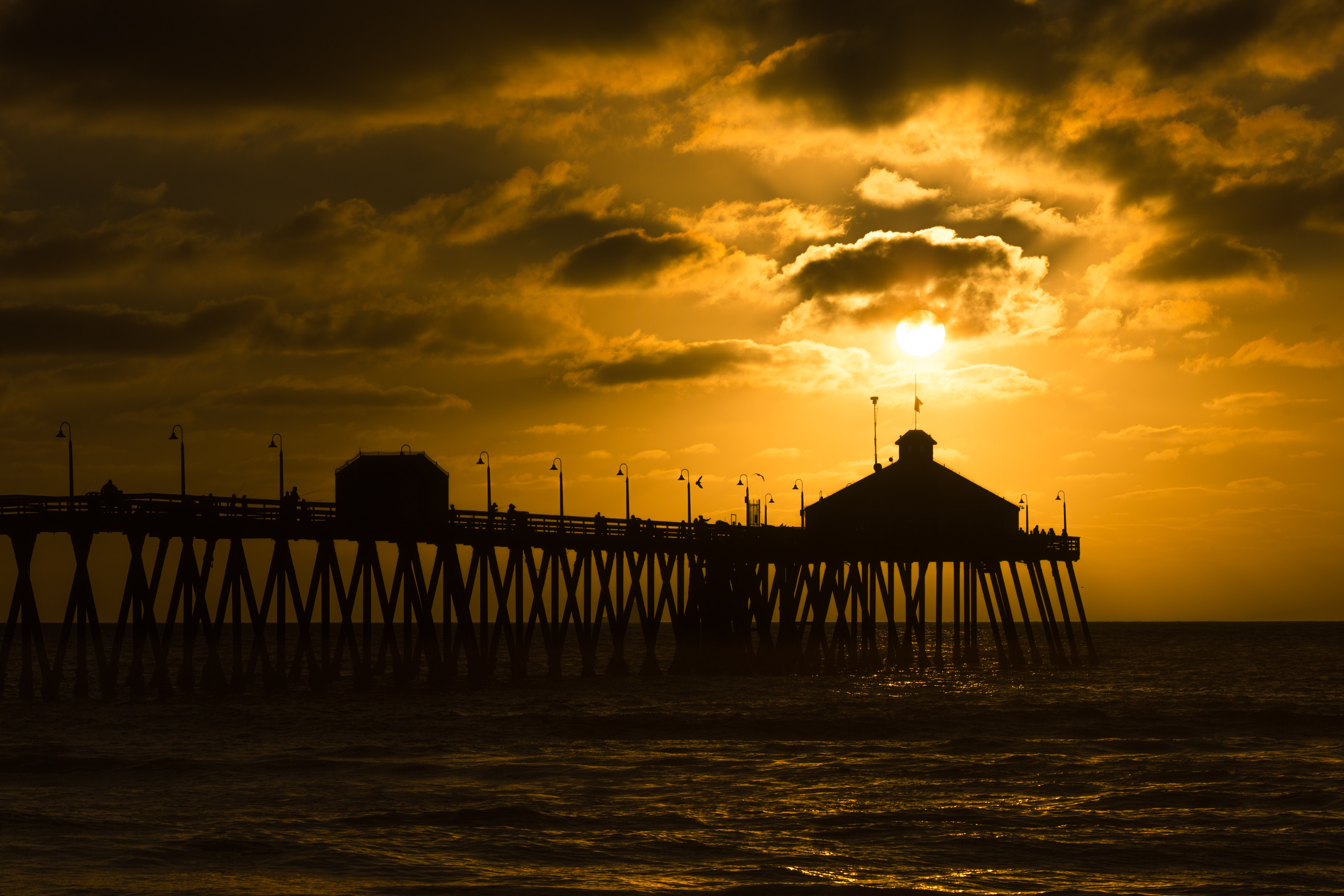 silhouette photo of sea dock at golden hour