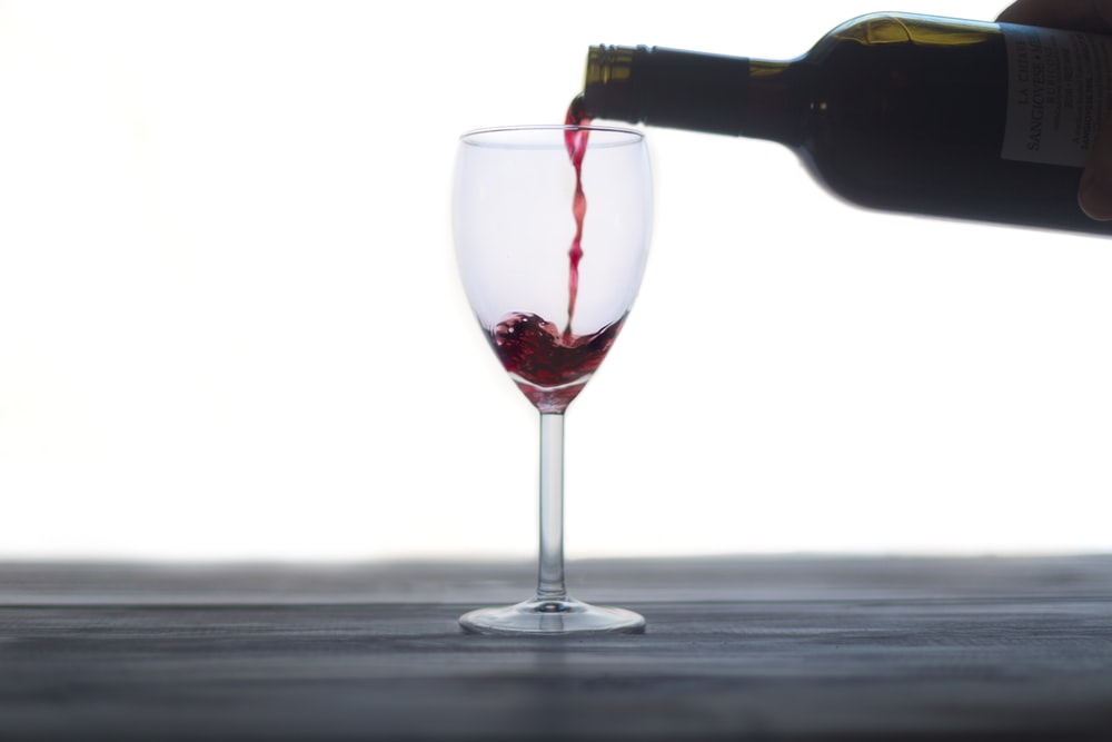 wine bottle pouring on clear wine glass