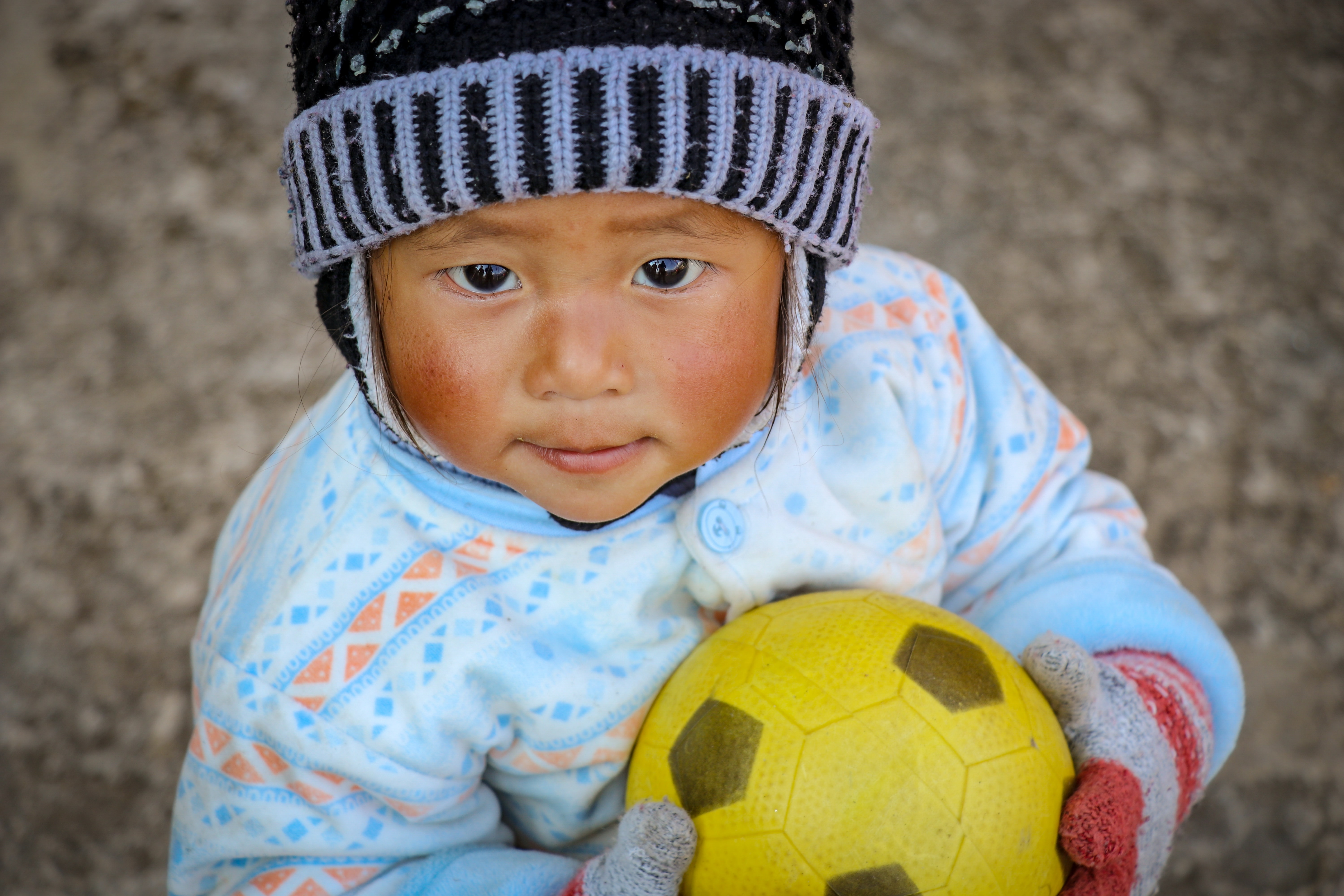 baby in blue and white shirt holding a ball