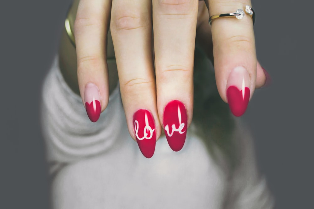 selective focus photography of woman's pink manicure