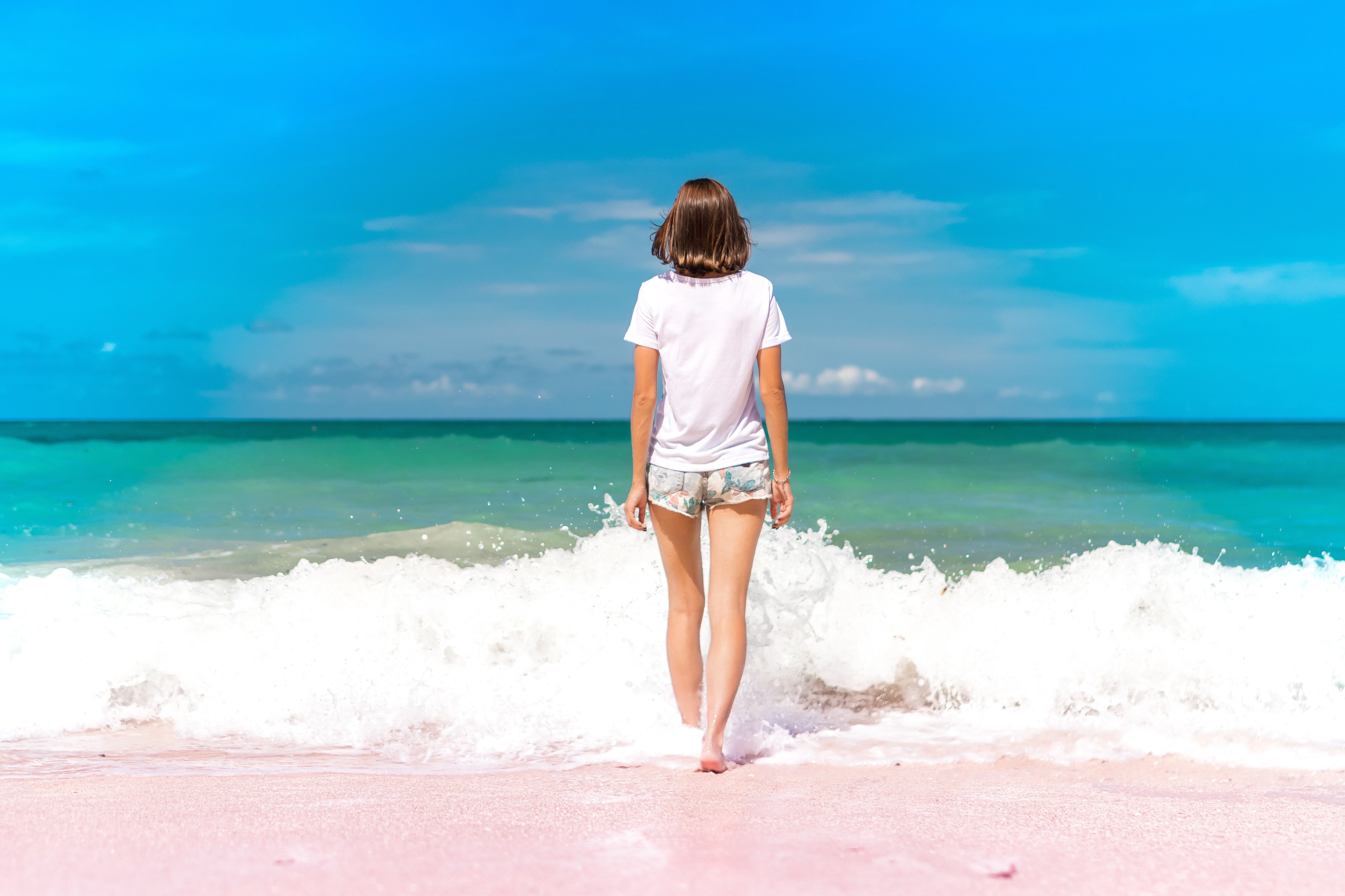 time lapse photography of woman standing in front of sea waves