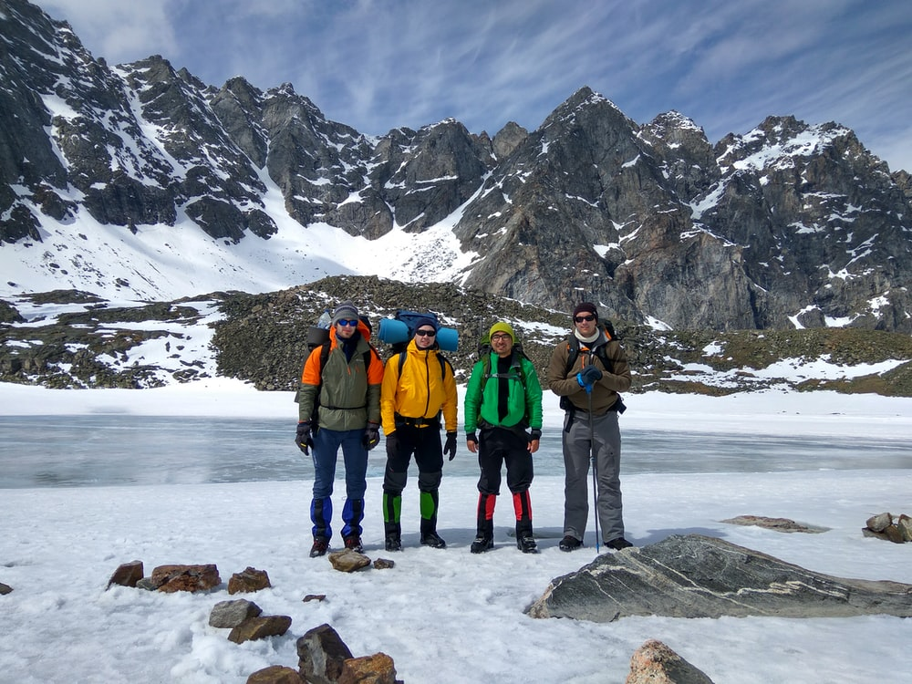 four men taking group photo in front of snow mountain