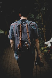 man facing backwards while holding DSLR camera