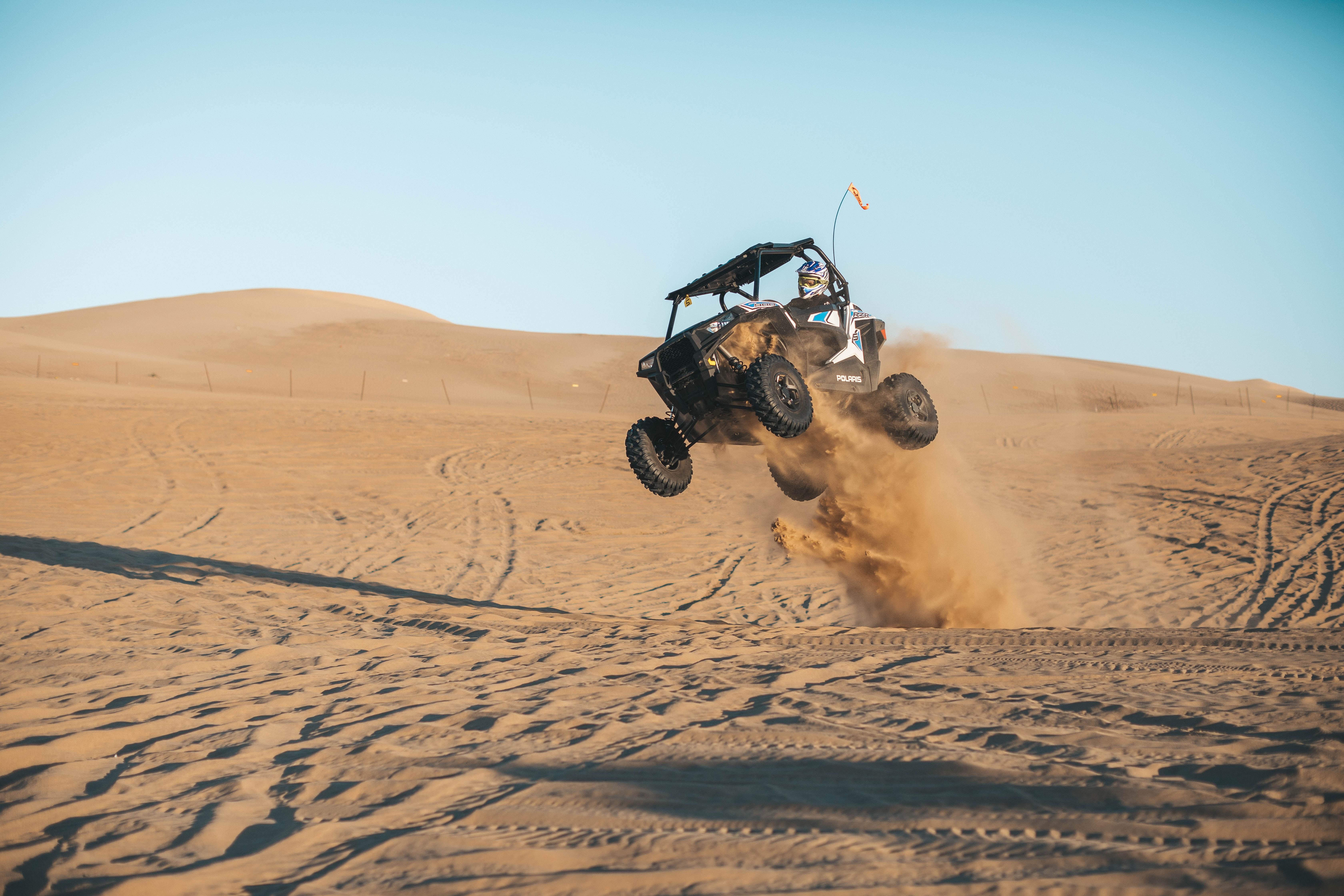 man riding on UTV on desert during daytime