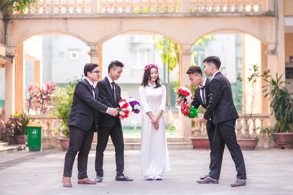 woman standing between four men