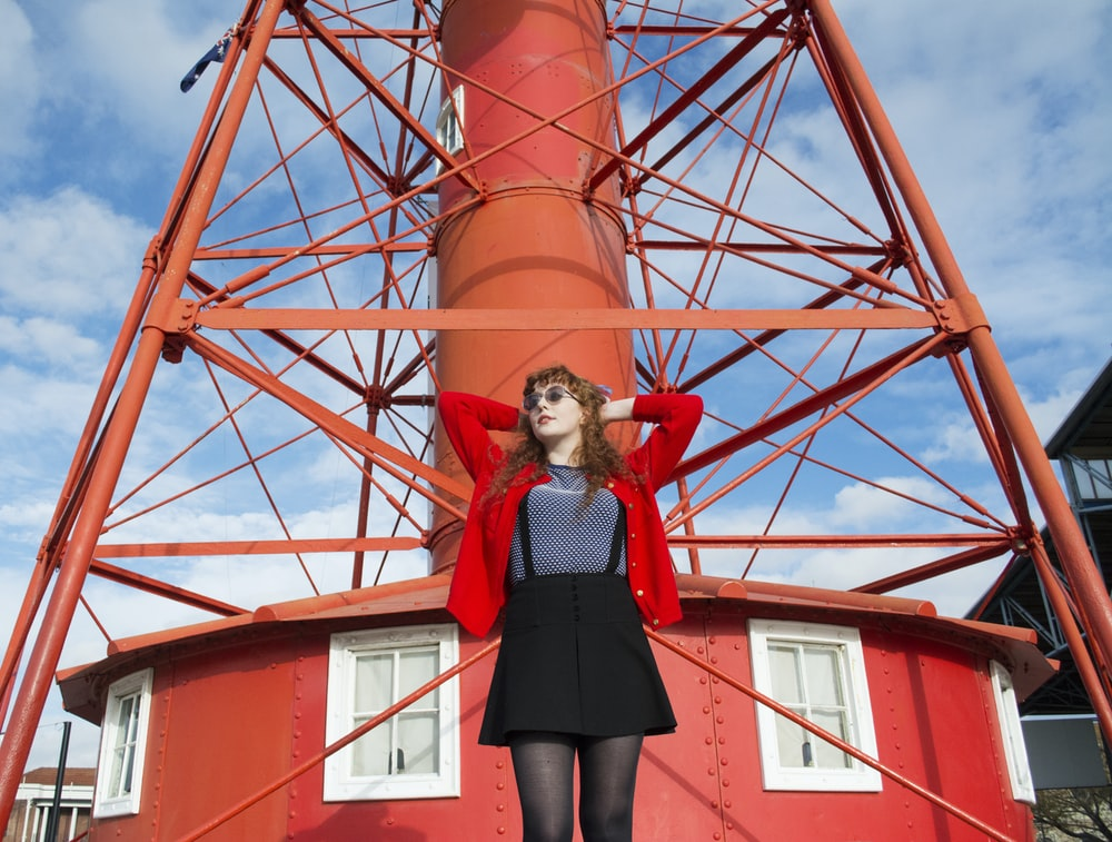 woman standing under red metal tower