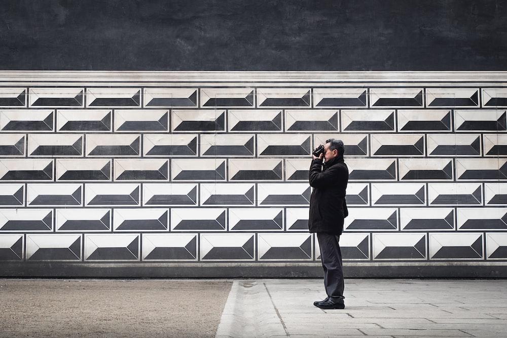 man holding camera near wall