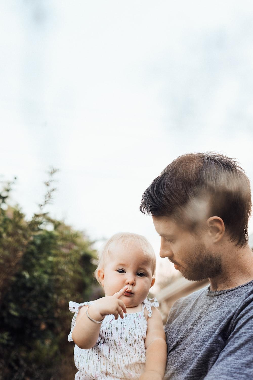 man holding baby in white shirt