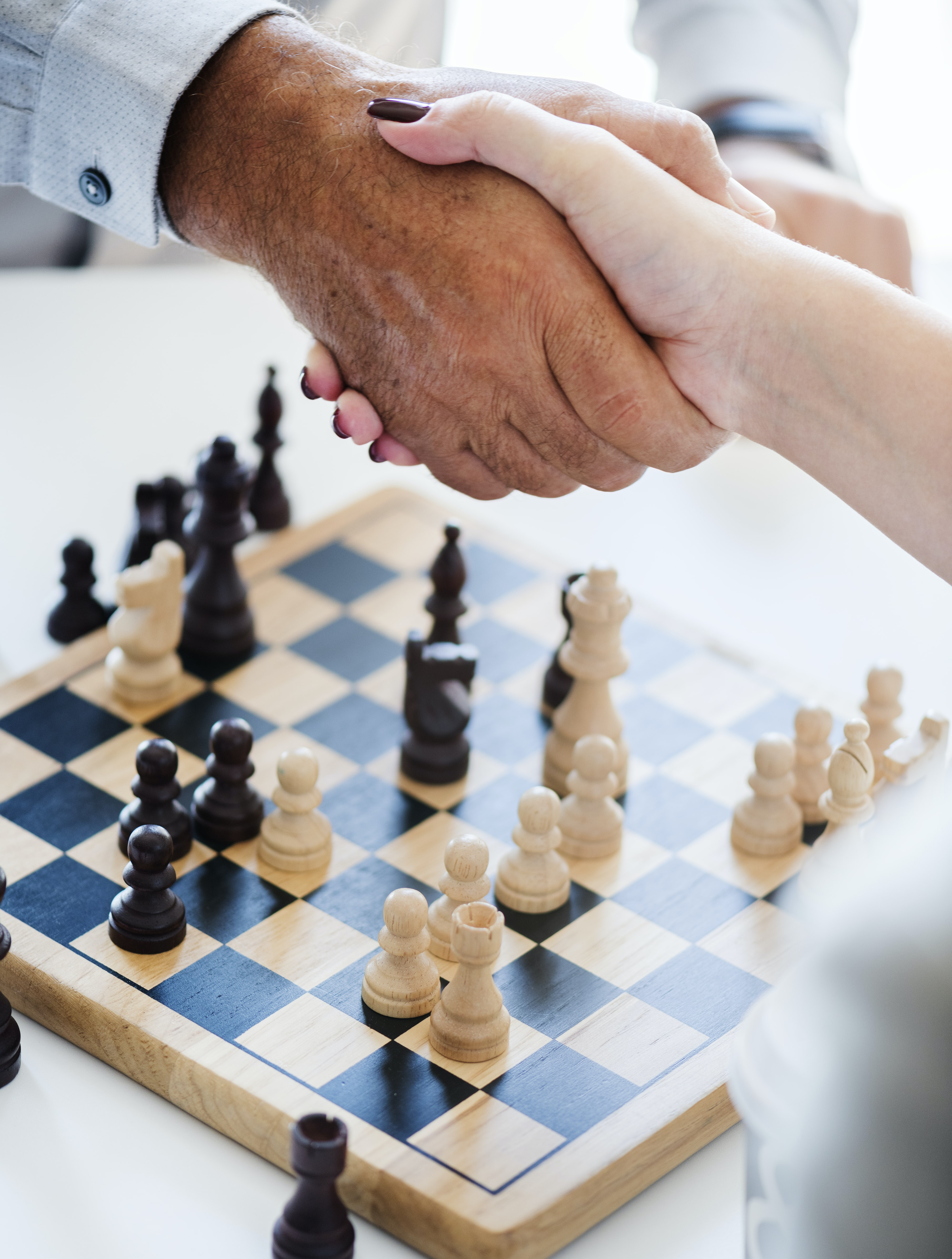 person shaking hands on top of chessboard