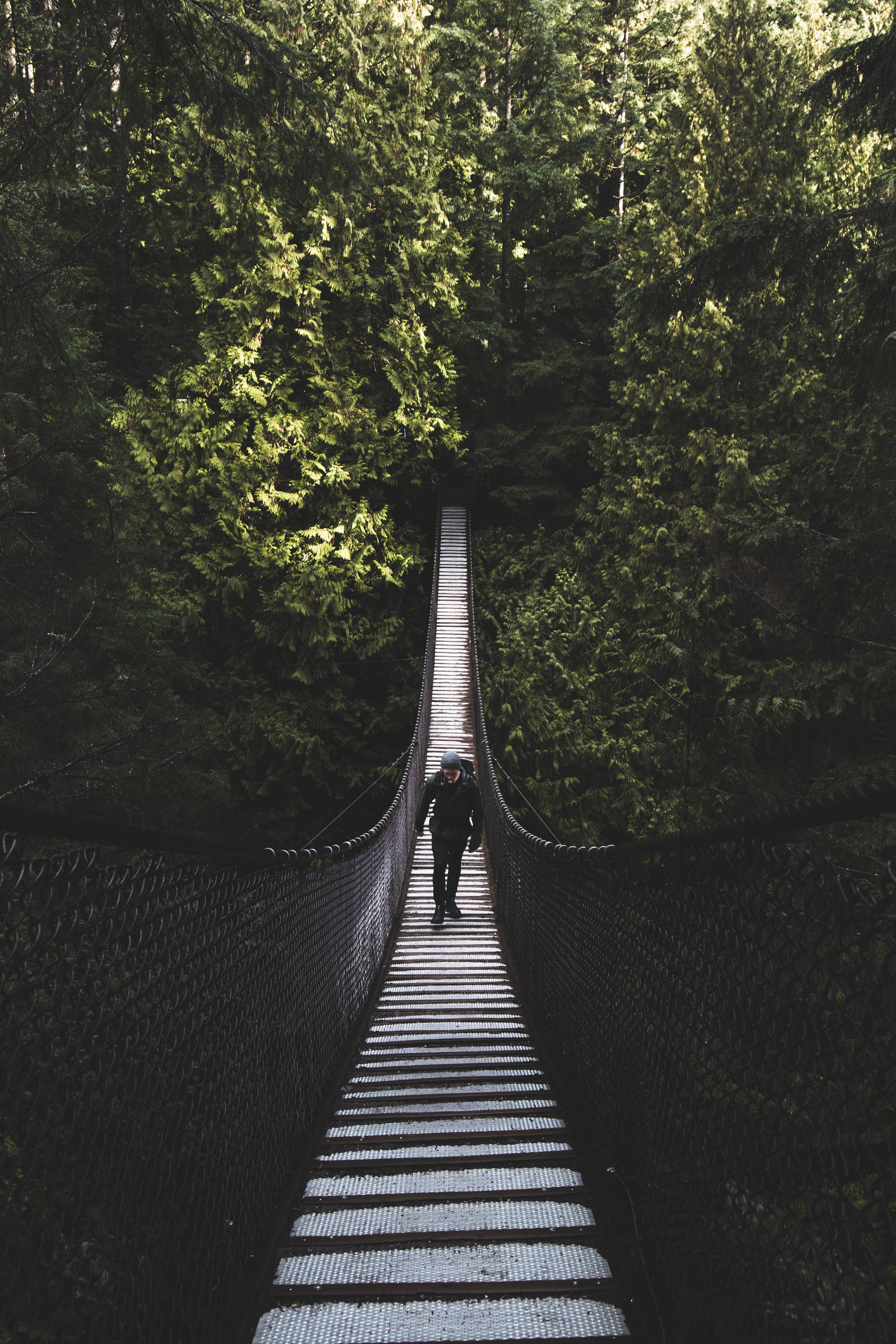 photo of man walking of foot bridge