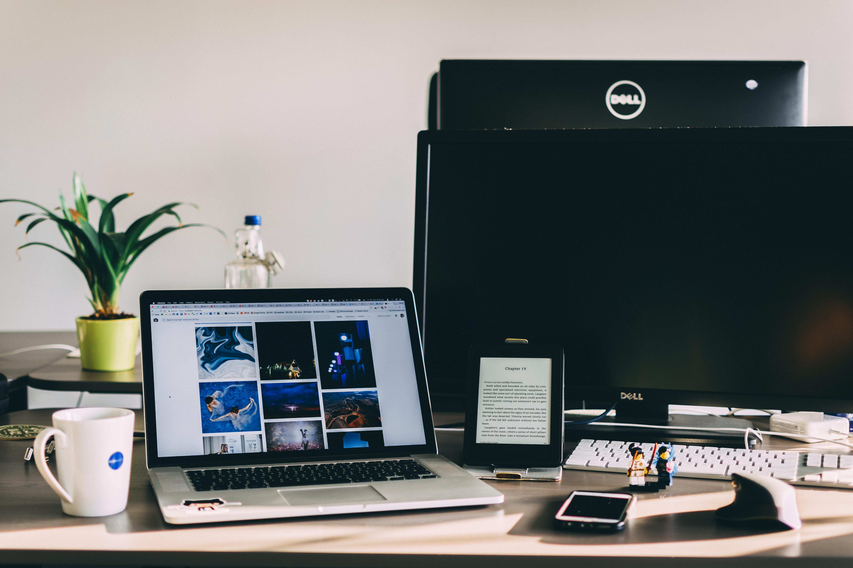 black and gray laptop computer near flat screen monitor
