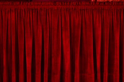 closeup photo of red rod pocket curtain curtain teams background