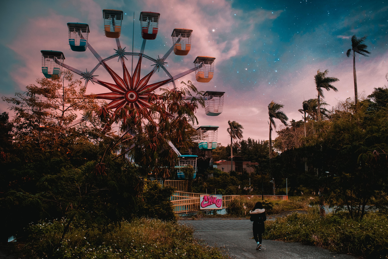 person walking towards amusement park with ferris wheel