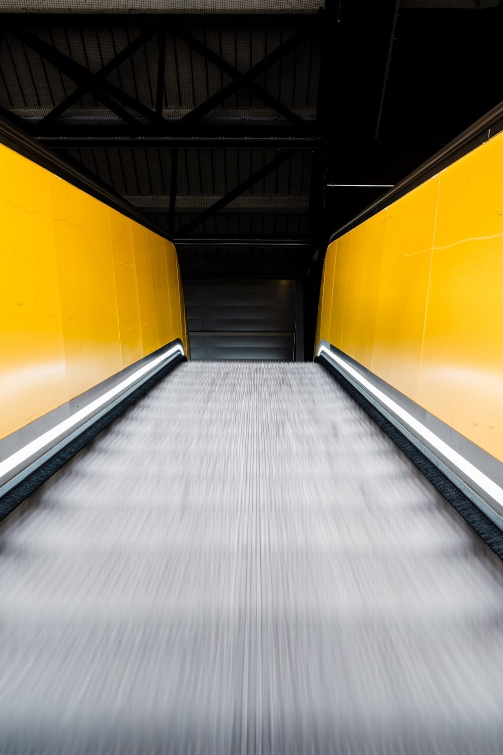 moving escalator with yellow handrails