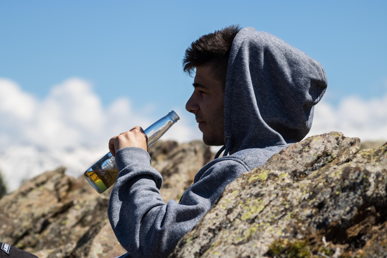 man drinking on bottle under sunny sky