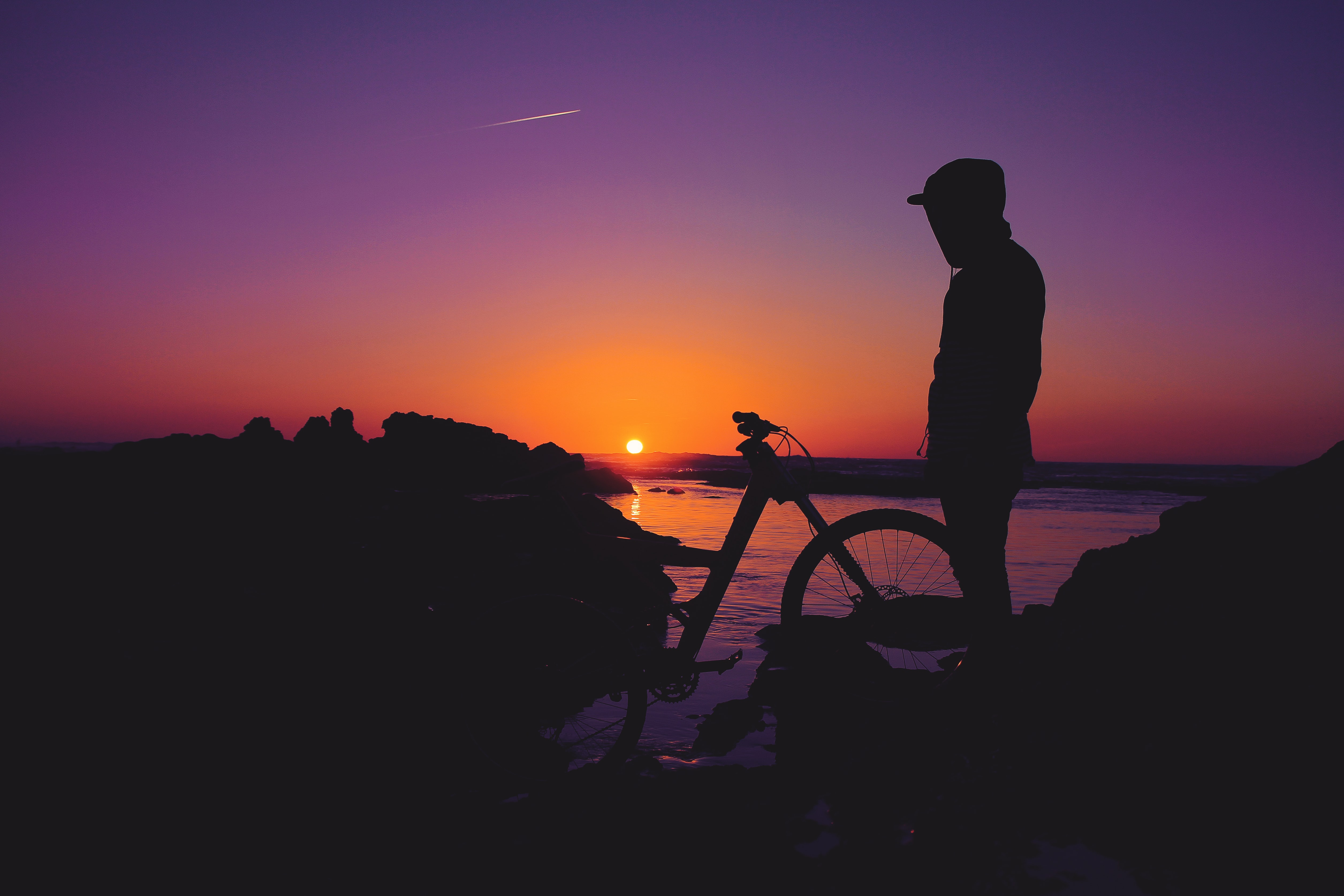 silhouette of person standing near bicycle