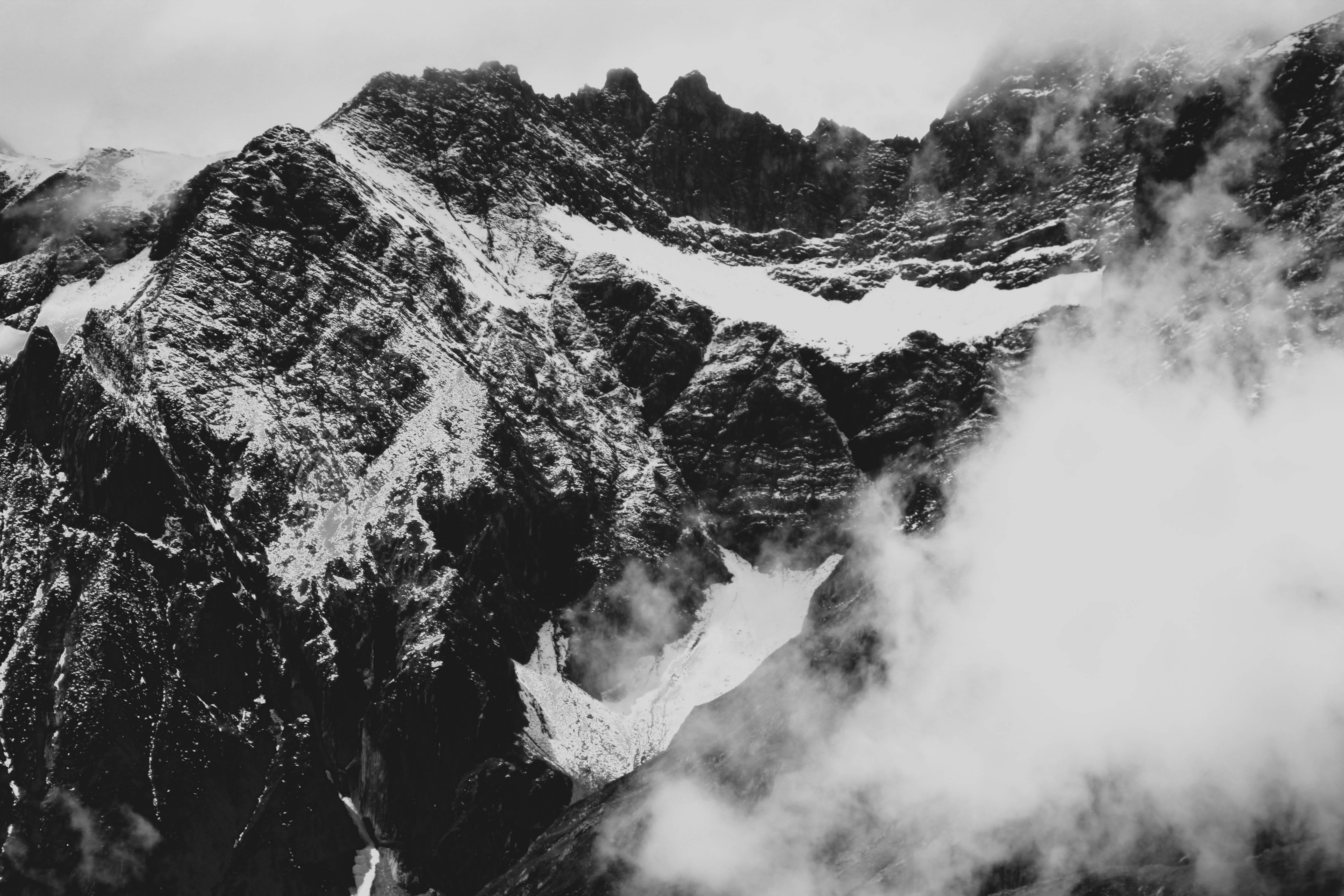 grayscale photography of glacier mountain with fogs