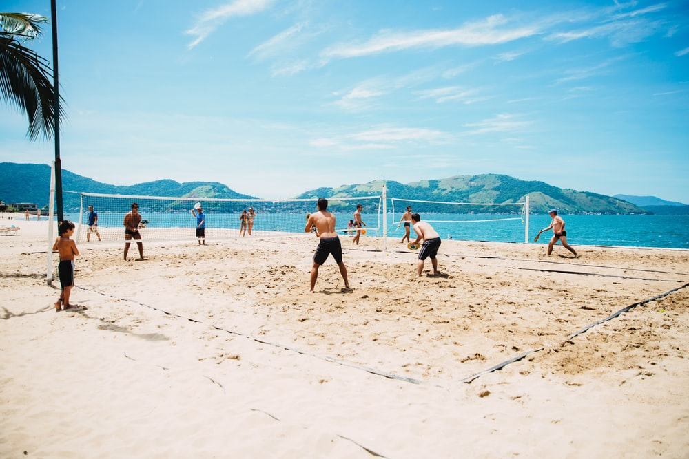 men playing volleyball on sand
