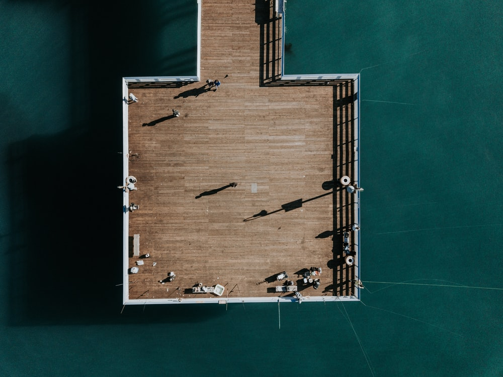 bird's-eye view photography of wooden dock on body of water