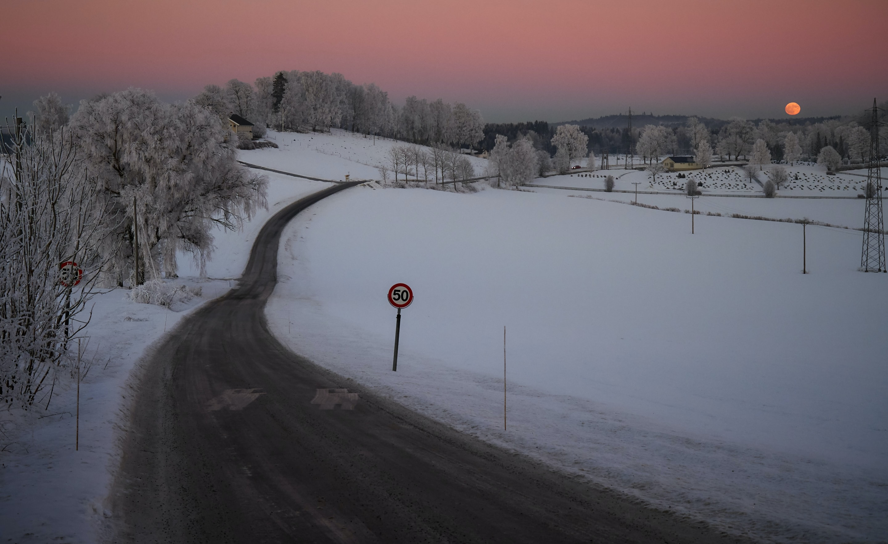 gray asphalt road between white snow field during sunset