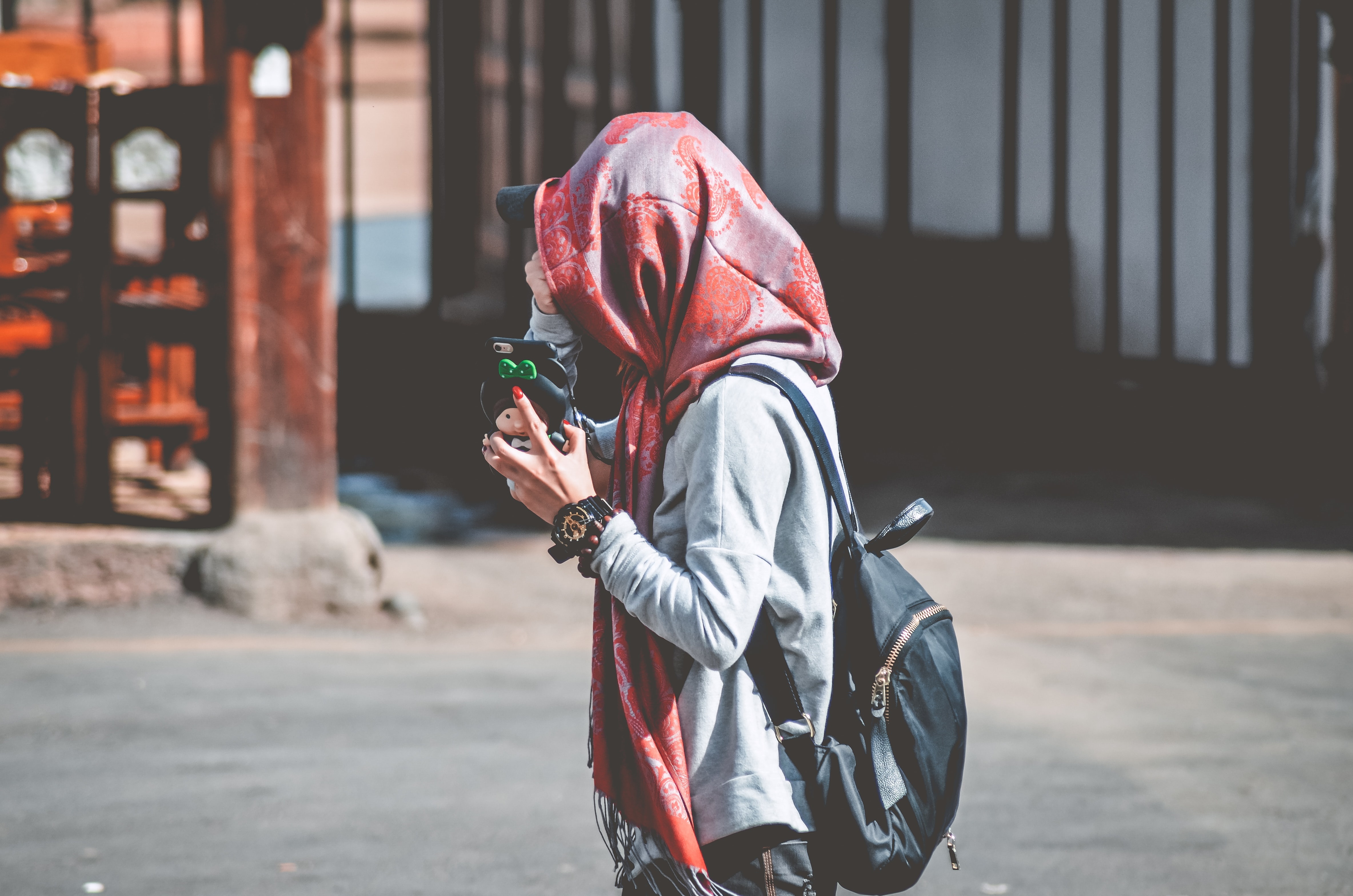 photo of woman wearing red and grey floral hijab scarf and carrying black leather backpack walking on street