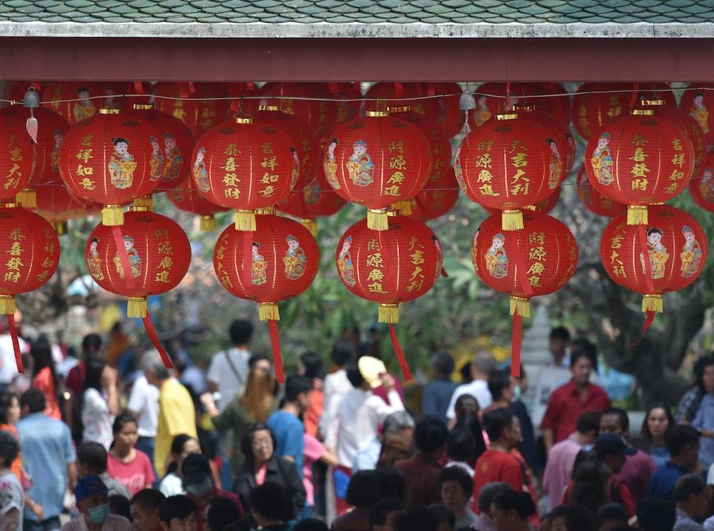 hanging round red lanterns near crowd at daytime
