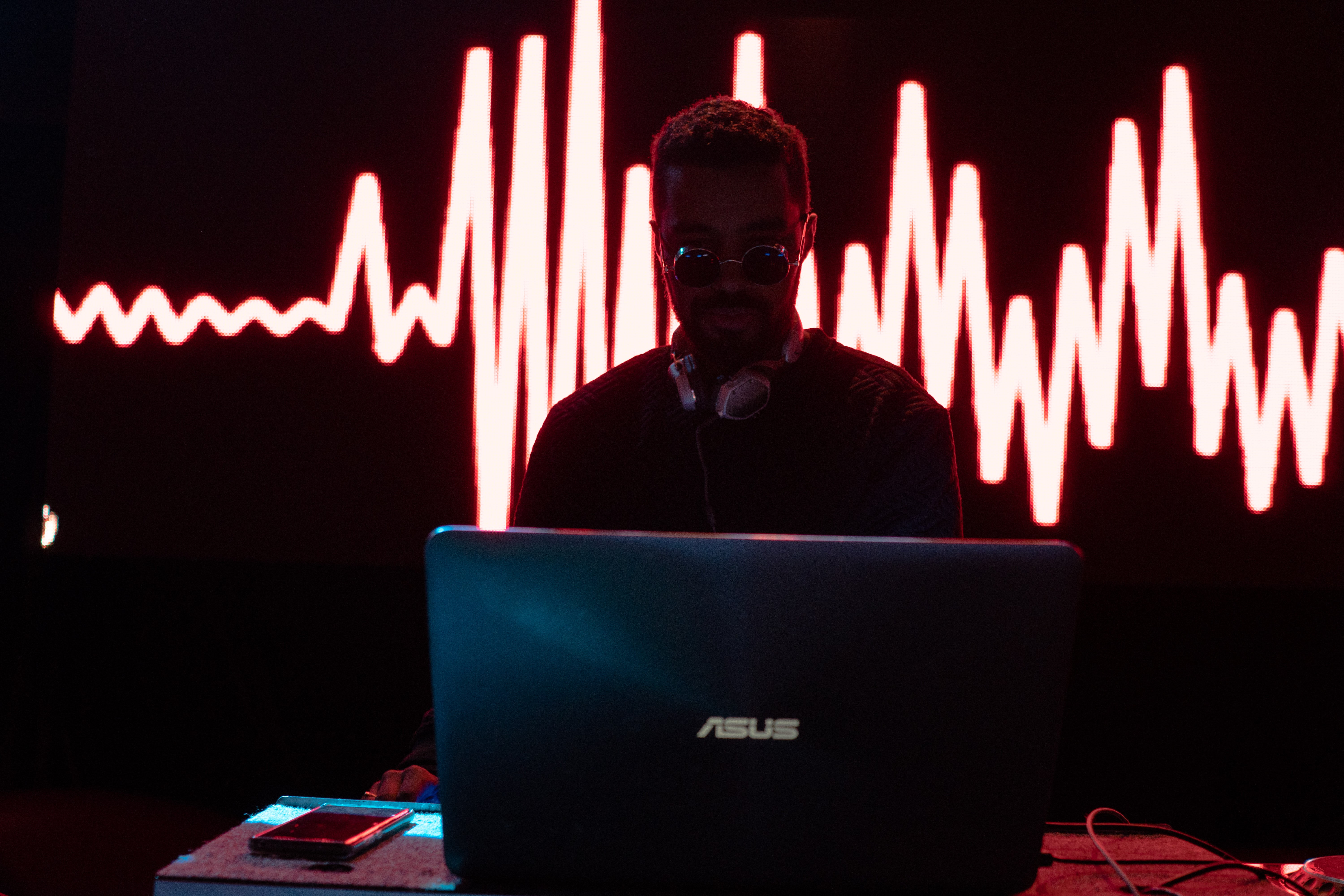 man standing in front Asus laptop
